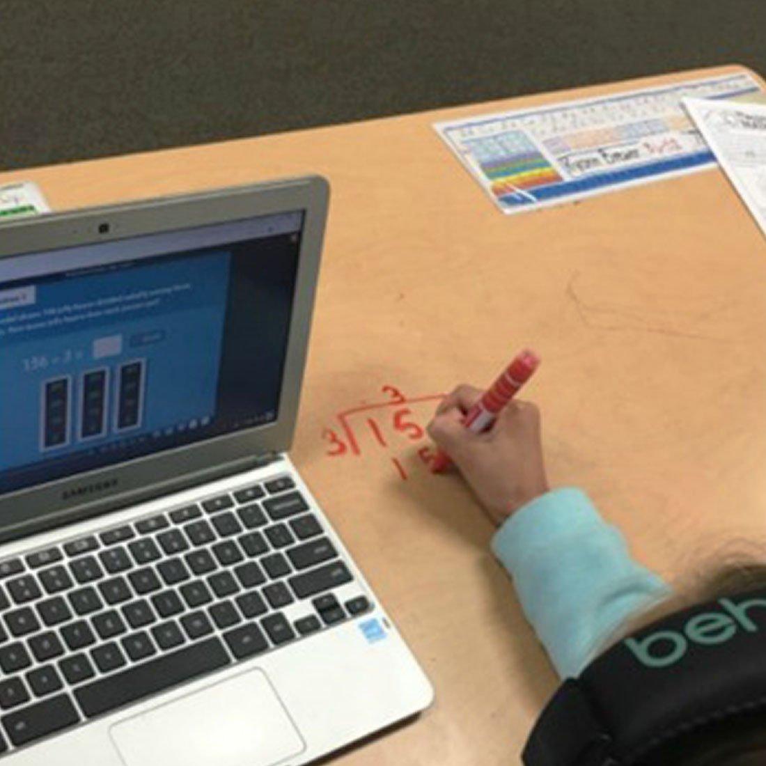 student-solving-math-problem-on-desk-in-expo-marker.jpg