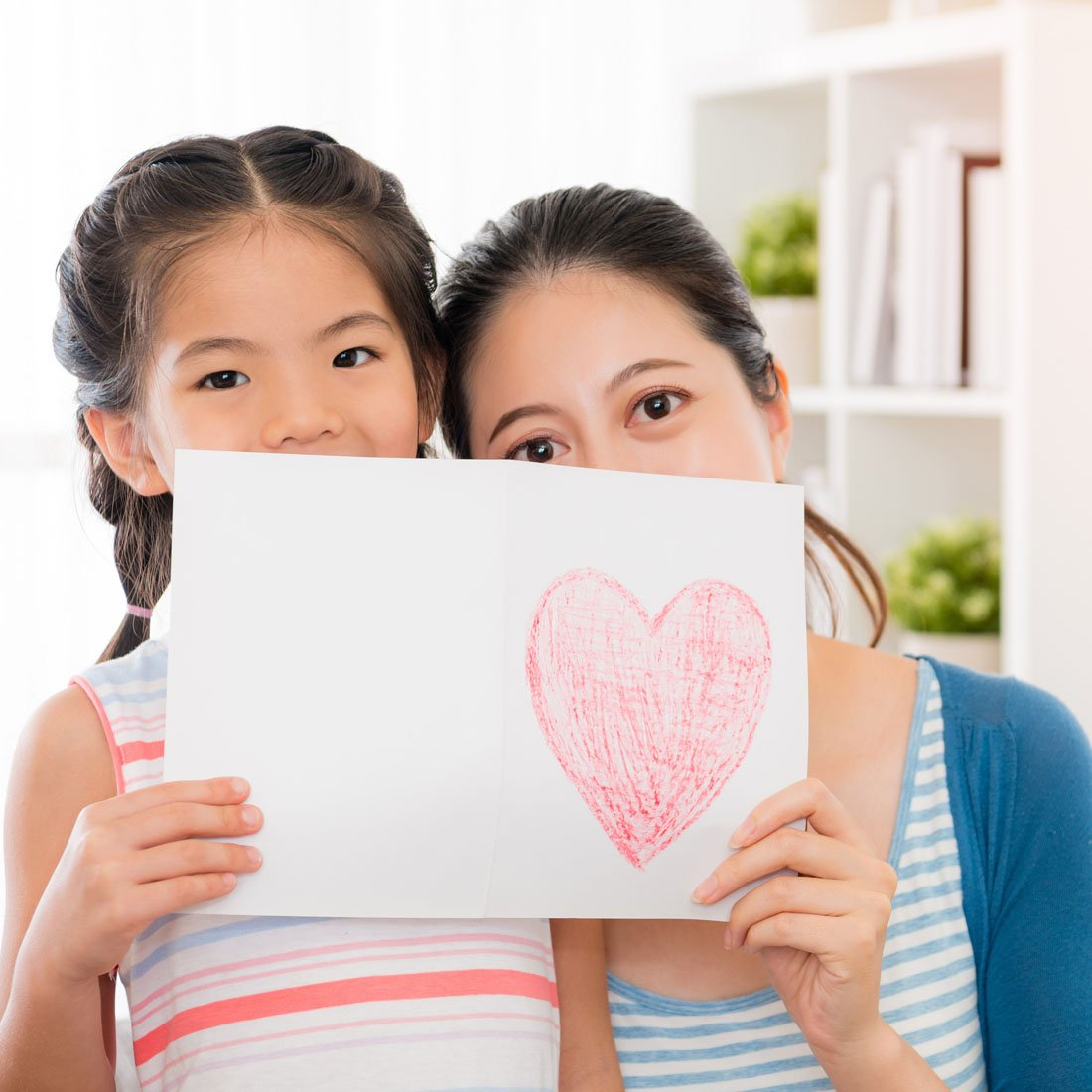 mom-and-daughter-holding-drawing-of-heart.jpg